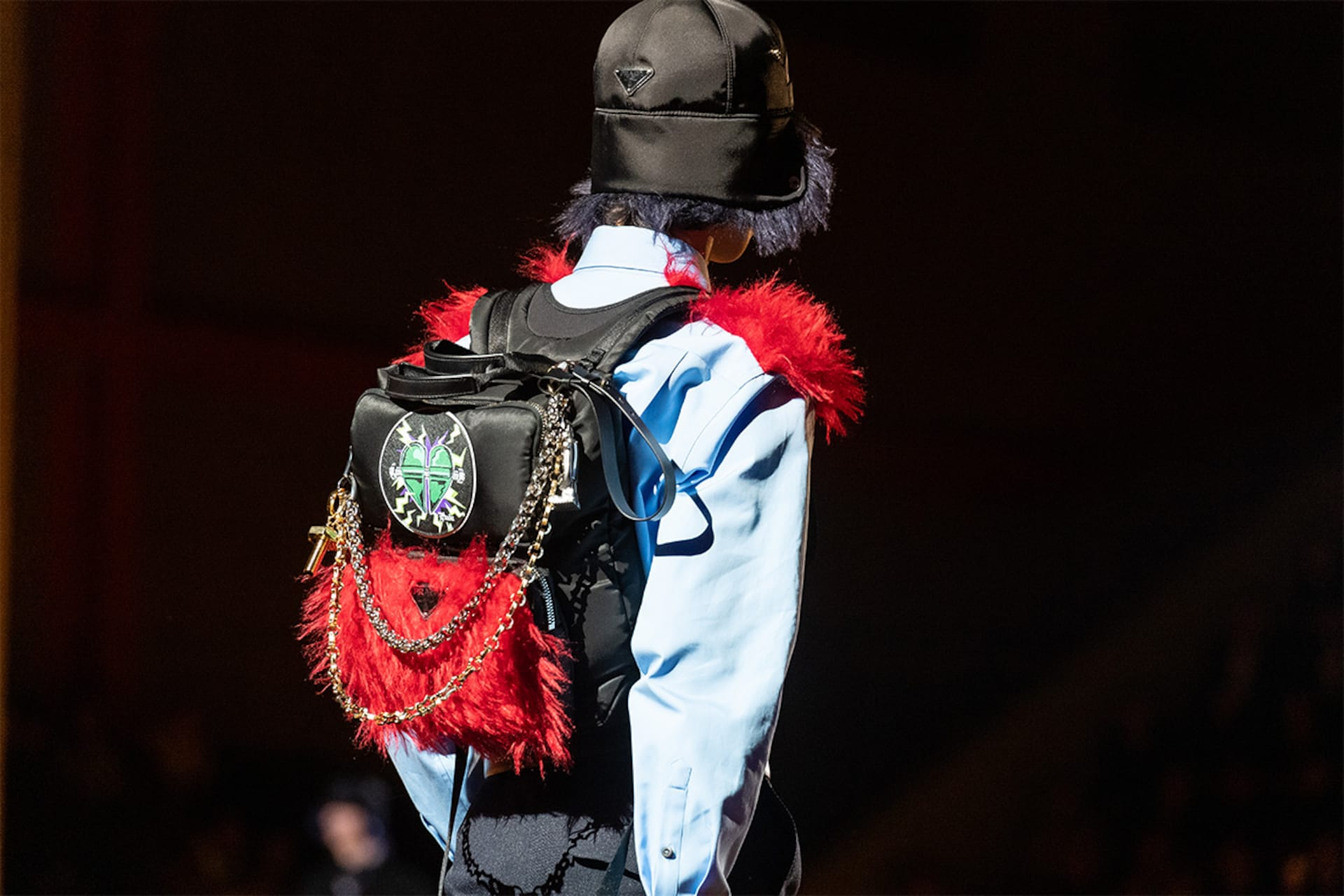 Prada Fall Winter 2019 Men's and Women's fashion show detail 1 with backpack and hat