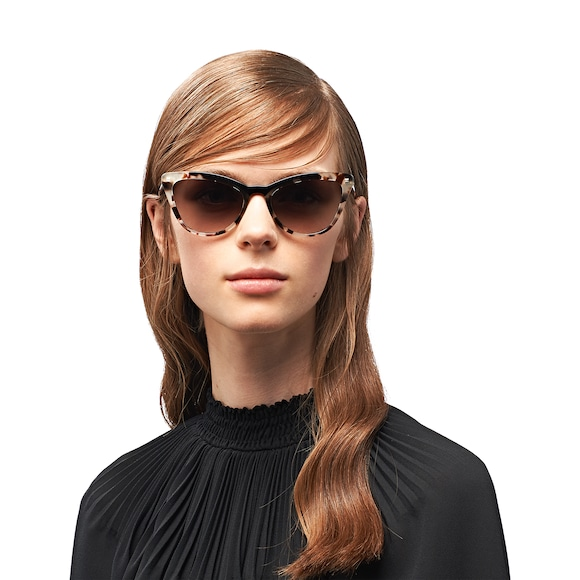 ded2e314fea Sunglasses from the Prada Ultravox collection. Feminine cat-eye silhouette  with sleek lines. Distinctive colored acetate inserts on the frame front.